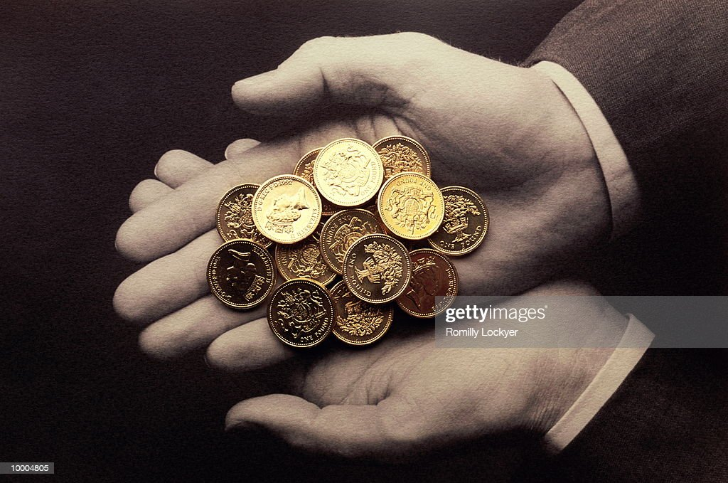 HANDS HOLDING UK ONE POUND COINS : Stock-Foto