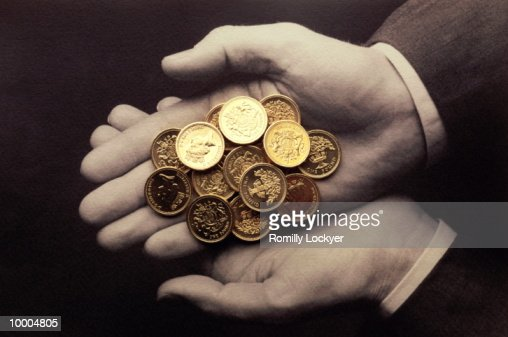HANDS HOLDING UK ONE POUND COINS : Stock Photo