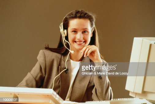WOMAN IN HEADSET AT OFFICE COMPUTER : Stock Photo