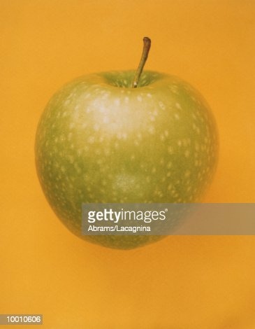 SPOTTED GREEN APPLE ON ORANGE BACKGROUND : Stock Photo