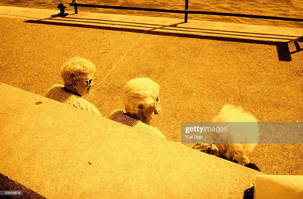 BACK VIEW OF THREE MATURE WOMEN BY WALL : Foto de stock