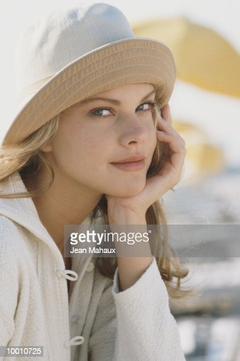 YOUNG WOMAN IN HAT WITH CHIN ON HAND : Stock-Foto