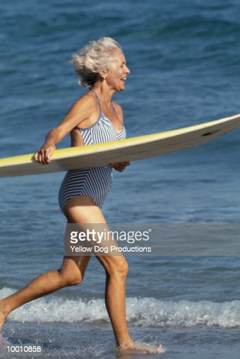 MATURE WOMAN WITH SURFBOARD ON BEACH : Foto de stock