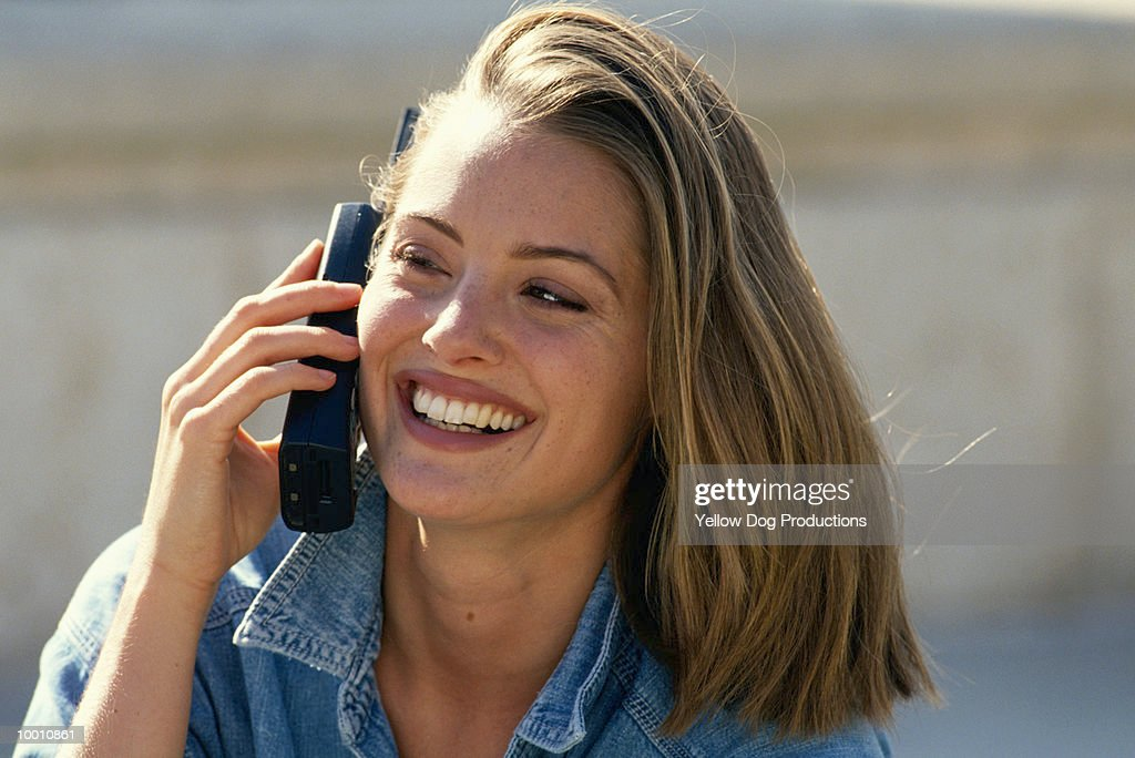 CLOSE-UP OF A YOUNG WOMAN ON PHONE OUTDOORS : Stock Photo