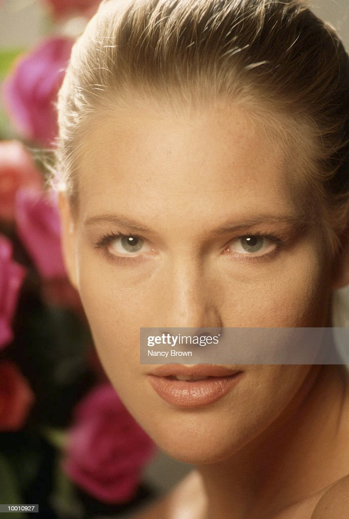CLOSE-UP OF A WOMAN'S FACE AND FLOWERS : Stock-Foto