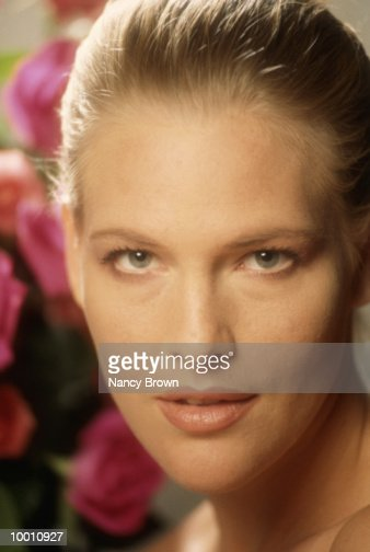 CLOSE-UP OF A WOMAN'S FACE AND FLOWERS : Foto de stock