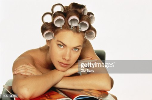 BARE SHOULDERED WOMAN WITH CURLERS IN HAIR : Stock Photo