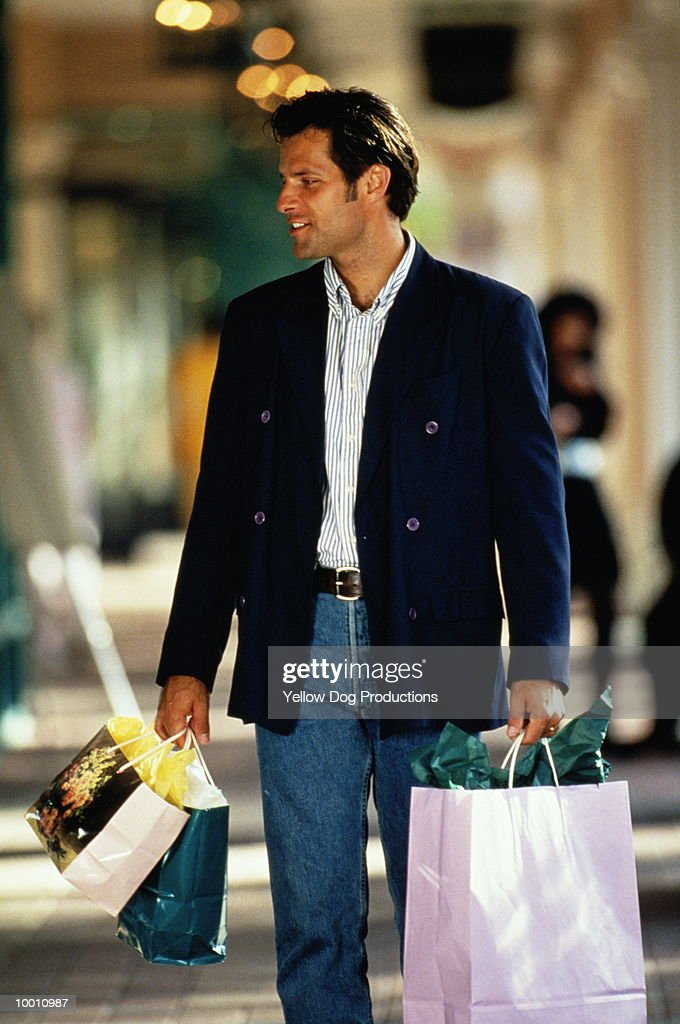MAN WITH COLORFUL SHOPPING BAGS AT MALL : Stock-Foto
