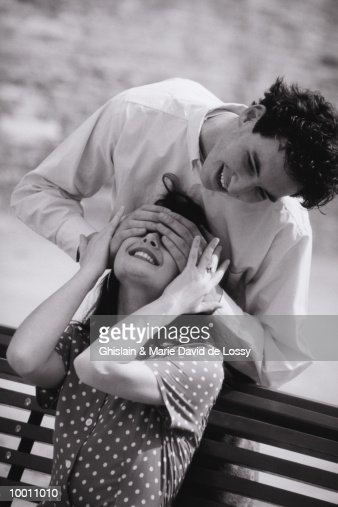 YOUNG MAN PLAYING GUESS WHO WITH WOMAN : Stock Photo