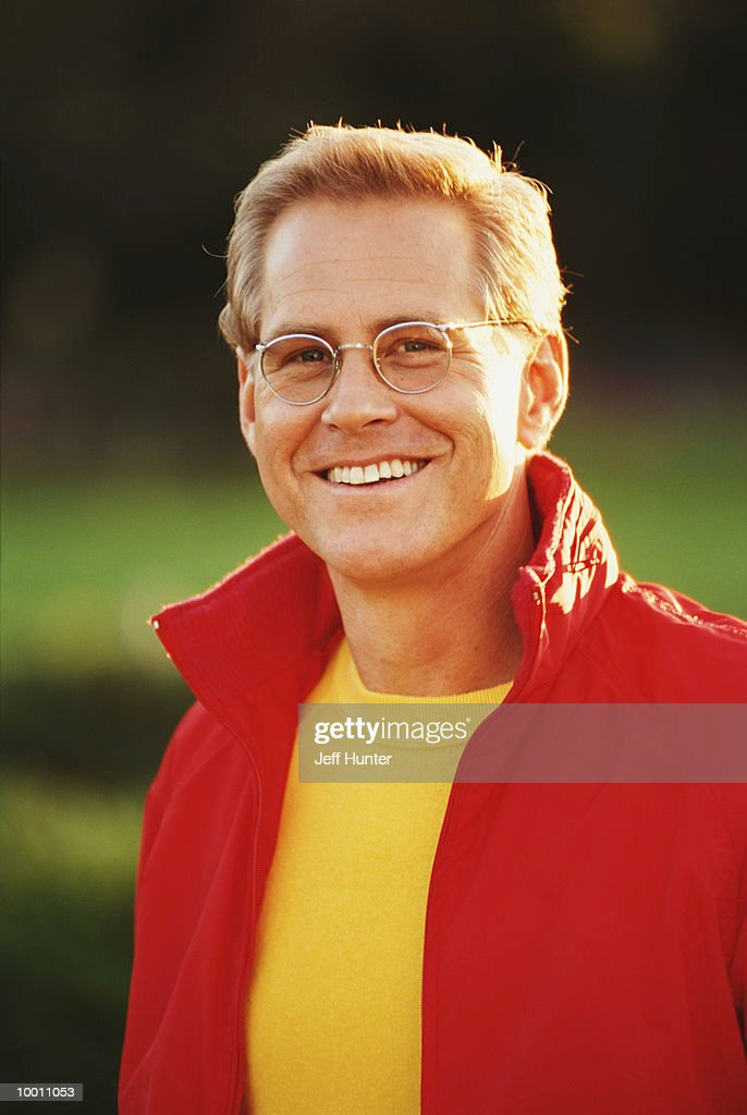 MIDDLE-AGED MAN IN RED JACKET OUTDOORS : Stock Photo