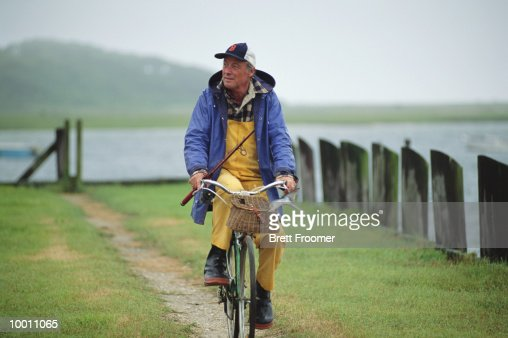 MATURE MAN WITH FISHING GEAR ON BICYLCLE : Stock Photo