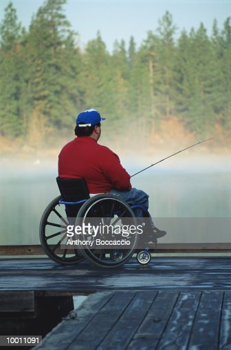 MAN IN WHEELCHAIR FISHING OFF DOCK IN WASHINGTON : Stock Photo
