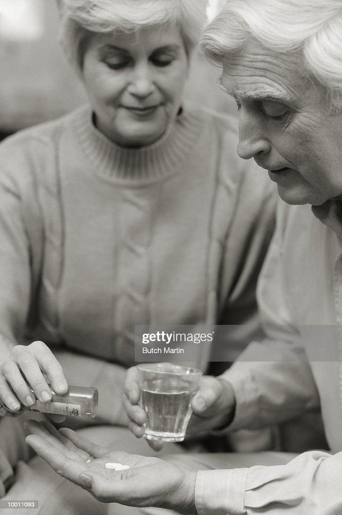 MATURE WOMAN GIVING MAN HIS MEDICATION : Stock Photo