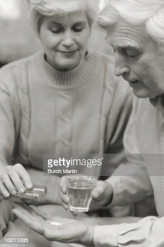 MATURE WOMAN GIVING MAN HIS MEDICATION : Foto de stock