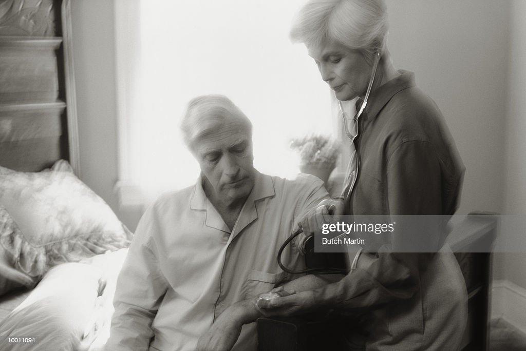 MATURE WOMAN TAKING MAN'S BLOOD PRESSURE : Stock-Foto