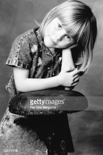 PORTRAIT OF A GIRL LEANING ON STOOL : Stock Photo