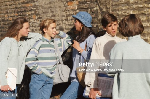 GROUP OF TEENAGERS TALKING BY BRICK WALL : Stock-Foto