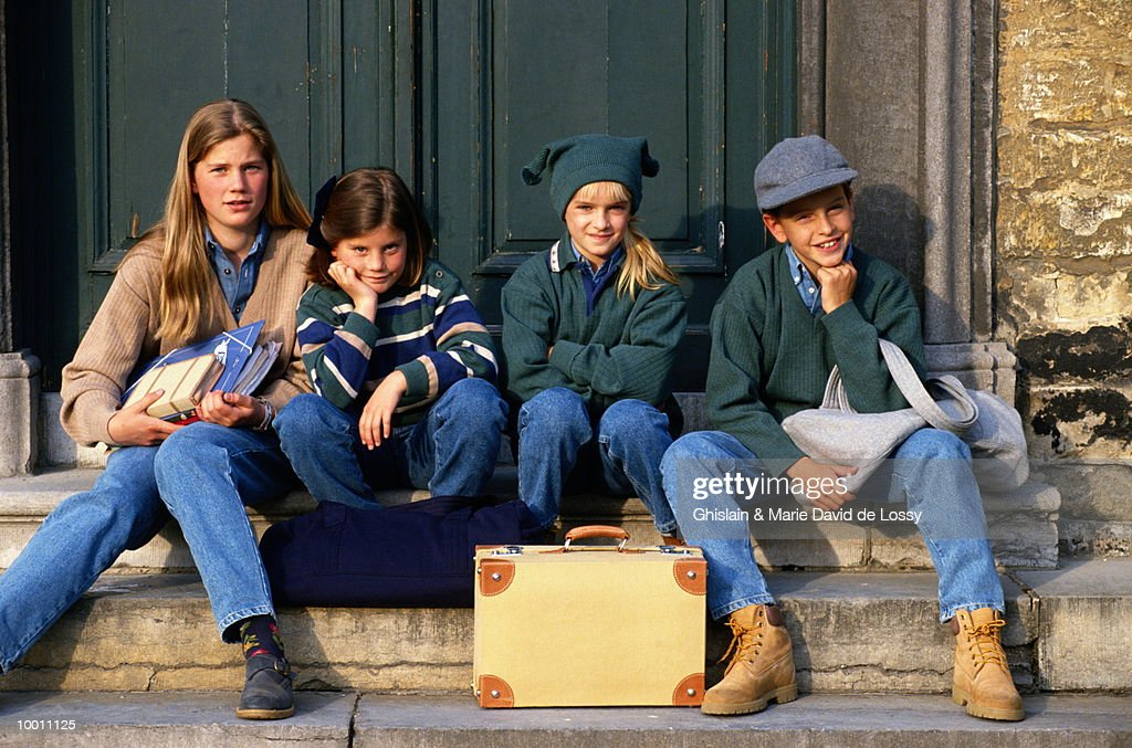 CHILDREN ON DOORSTEP WITH OVERNIGHT BAGS : Stock Photo