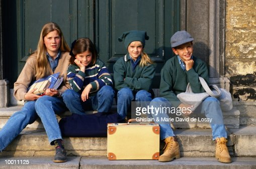 CHILDREN ON DOORSTEP WITH OVERNIGHT BAGS : Stock Photo