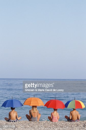 BACK VIEW OF CHILDREN ON BEACH WITH UMBRELLAS : Stock Photo