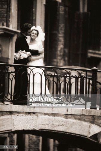 GROOM KISSING BRIDE ON BRIDGE IN VENICE : Stock Photo