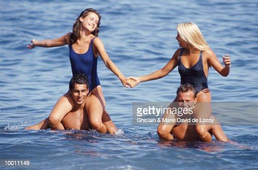 WOMEN ON MEN'S SHOULDERS IN OCEAN : Foto de stock