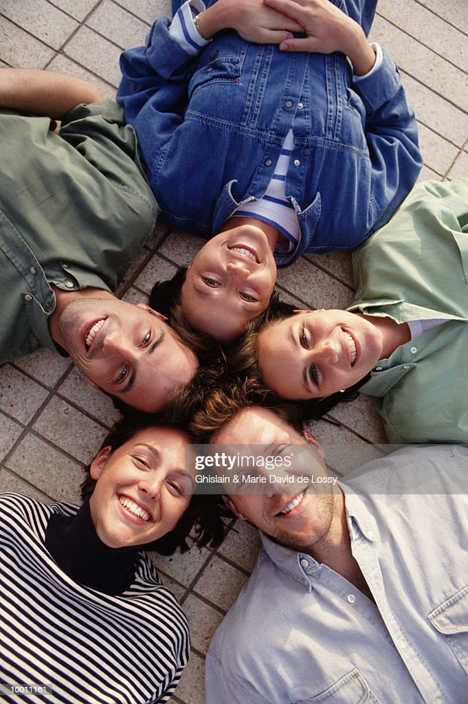PEOPLE LYING ON FLOOR WITH HEADS IN CIRCLE : Stock Photo