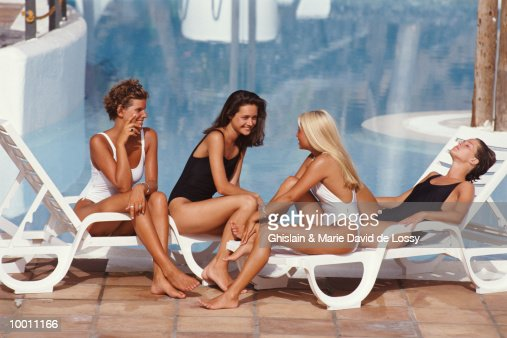 WOMEN IN SWIMSUITS RELAXING BY POOL : Stock Photo