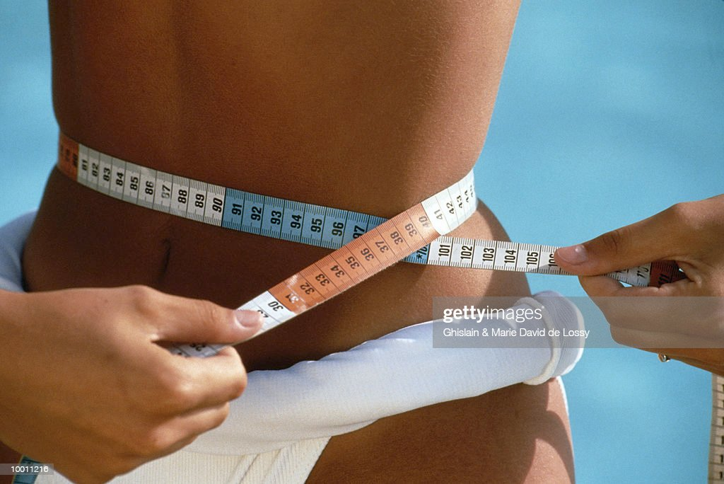 WOMAN IN BIKINI MEASURING WAIST : Stock Photo