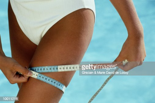 CLOSE-UP OF A WOMAN MEASURING LEG BY POOL : Stock Photo