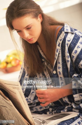 YOUNG WOMAN WITH GLASS OF MILK READING NEWS : Stock Photo