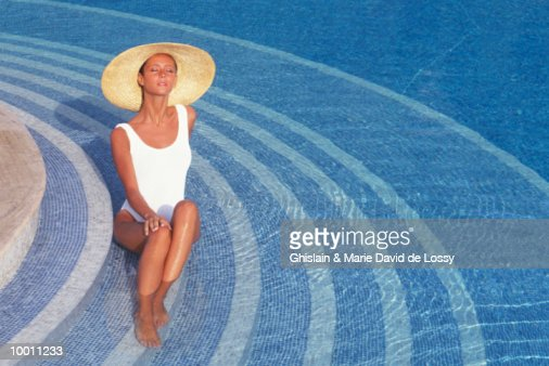 WOMAN IN SWIMSUIT & HAT ON STAIRS OF POOL : Stock-Foto