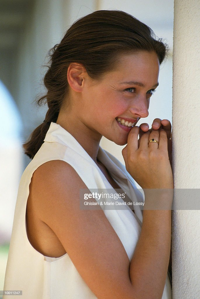 SMILING YOUNG WOMAN BY WHITE COLULMN : Stock Photo