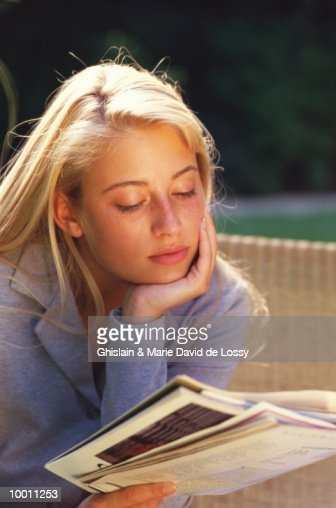 YOUNG BLONDE WOMAN READING OUTDOORS : Stock Photo