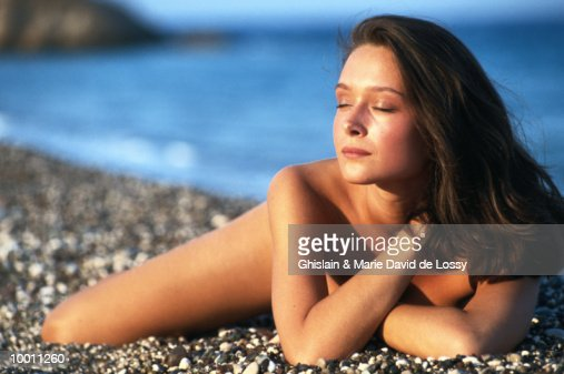 NUDE WOMAN LYING ON BEACH WITH EYES CLOSED : Foto de stock