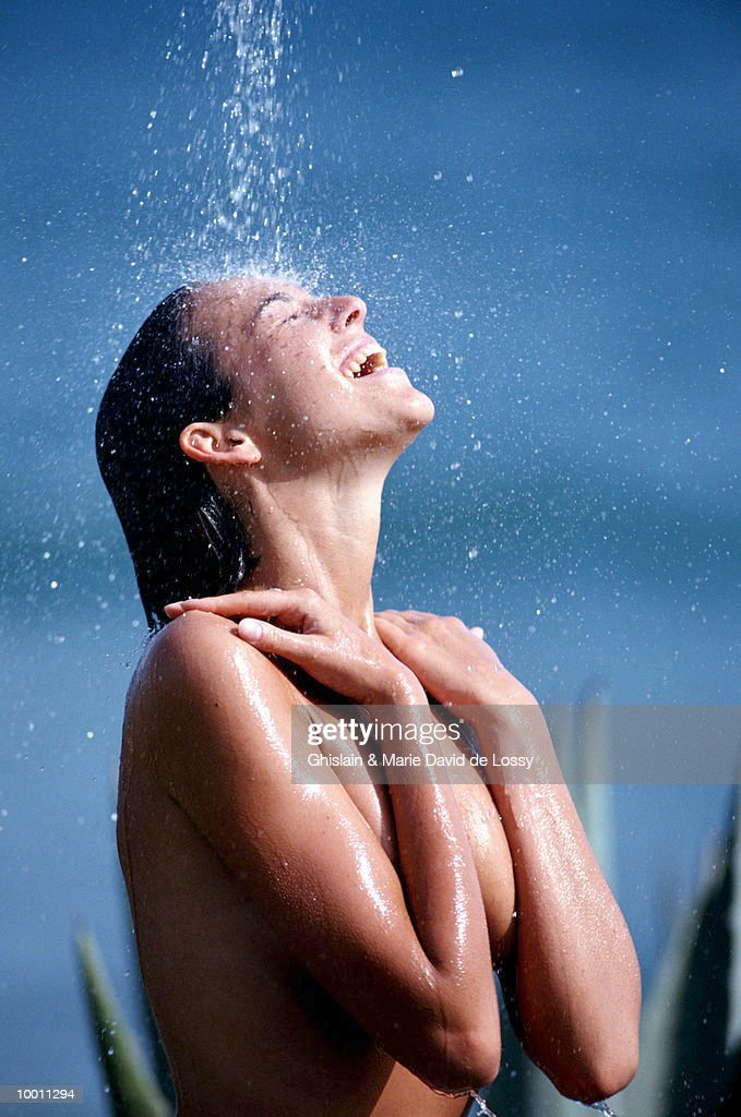 NUDE WOMAN ENJOYING OUTDOOR SHOWER : Stock Photo