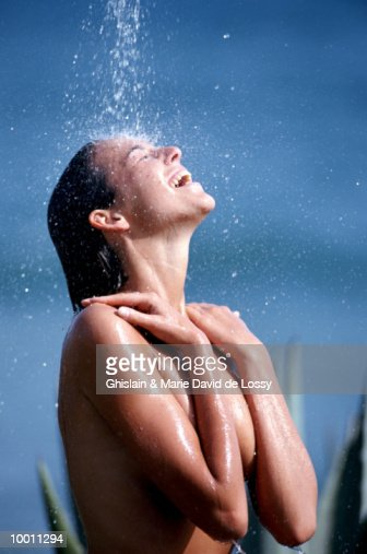 NUDE WOMAN ENJOYING OUTDOOR SHOWER : Stock-Foto