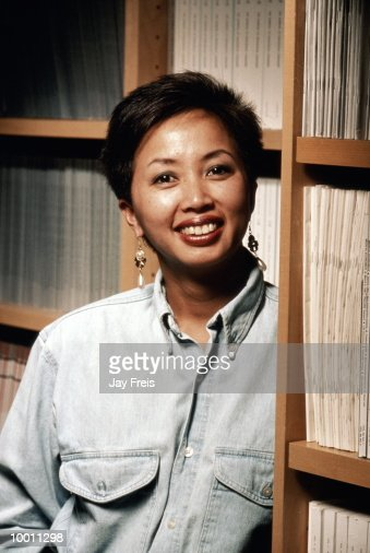 ASIAN WOMAN BY MAGAZINE SHELVES : Foto de stock