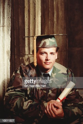 MALE GRADUATE IN CAMOUFLAGE CAP & GOWN : Stock Photo