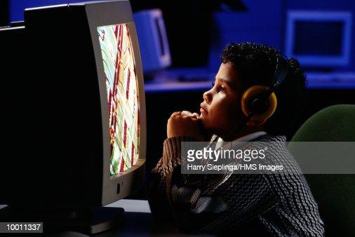 YOUNG BOY AT COMPUTER WITH HEADPHONES : Foto de stock