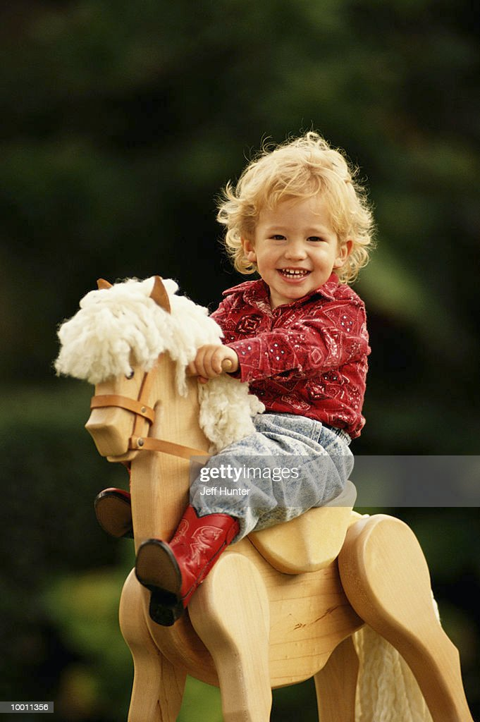 YOUNG BLOND BOY ON WOODEN HORSE : Foto de stock
