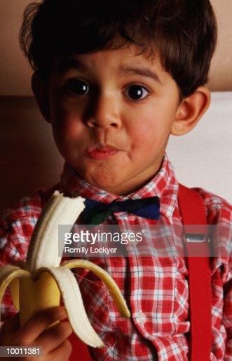 YOUNG BOY EATING BANANA : Stock Photo