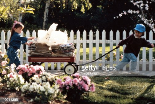 YOUNG BOY & GIRL WITH WAGON OF NEWSPAPERS : Stock Photo