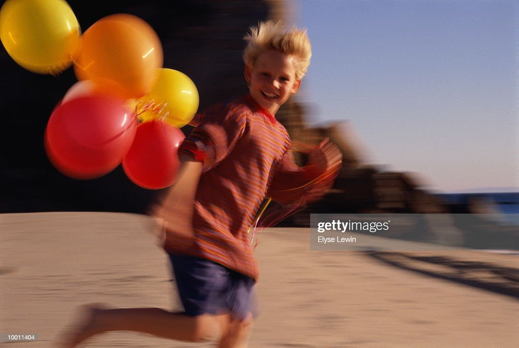 BOY WITH BALLOONS ON BEACH IN BLUR : Stock Photo