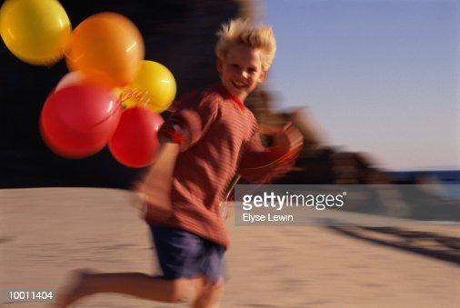 BOY WITH BALLOONS ON BEACH IN BLUR : Foto de stock