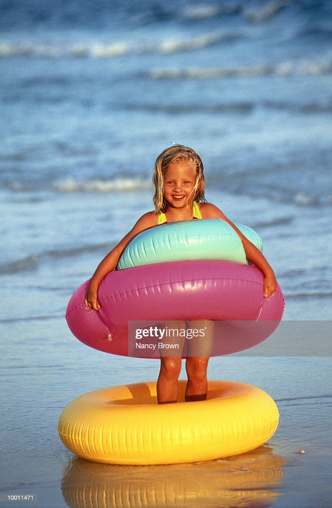 GIRL WITH COLORFUL INNER TUBES ON BEACH : Foto de stock