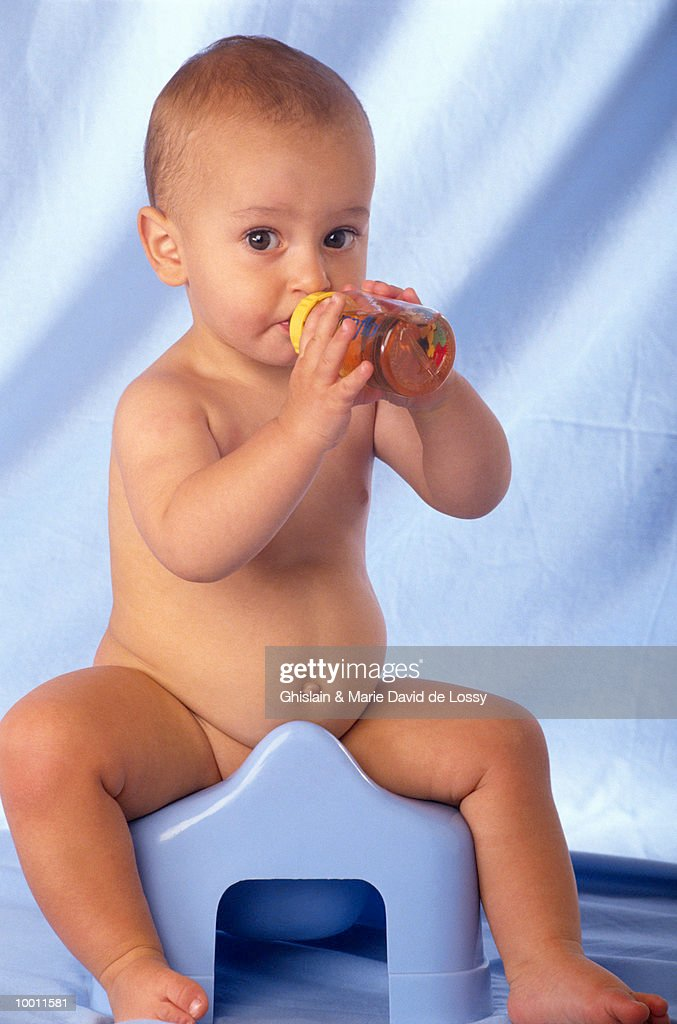 BABY WITH BOTTLE ON TRAINING POTTY : Stock Photo