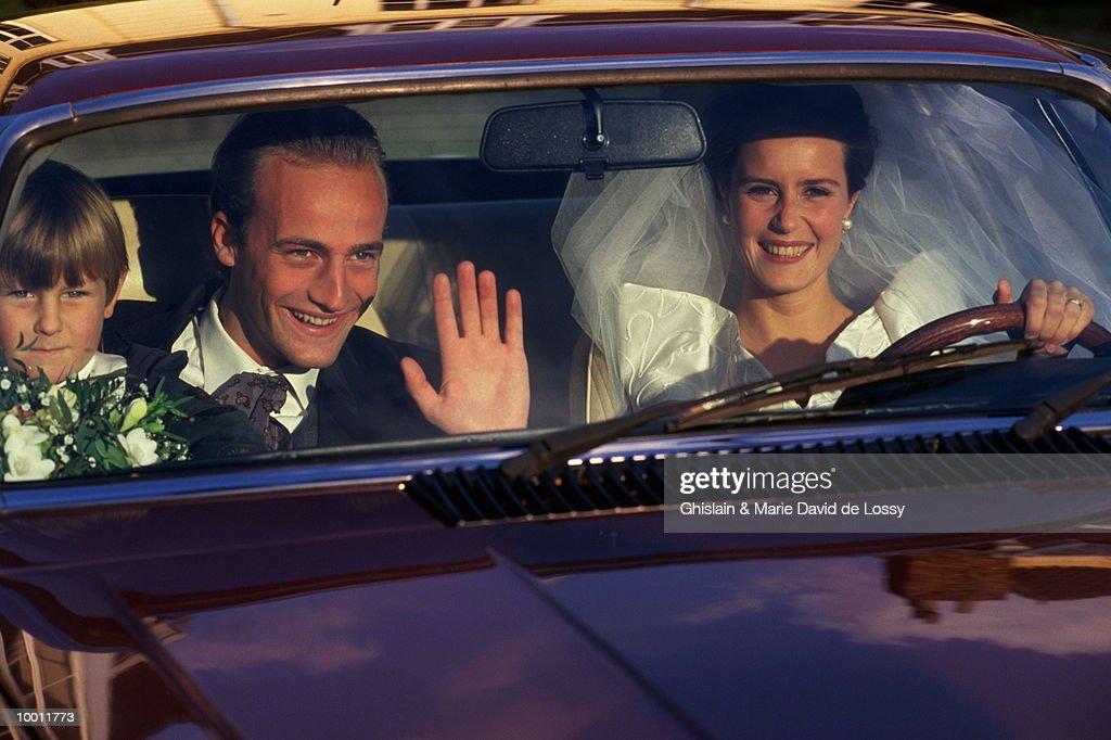 BRIDE & GROOM WITH BOY INSIDE CAR : Stock-Foto