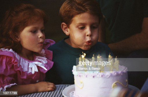 BIRTHDAY BOY BLOWING OUT CANDLES WITH SISTER : Stock Photo