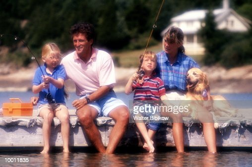 FAMILY WITH DOG FISHING OFF PIER : Stock Photo